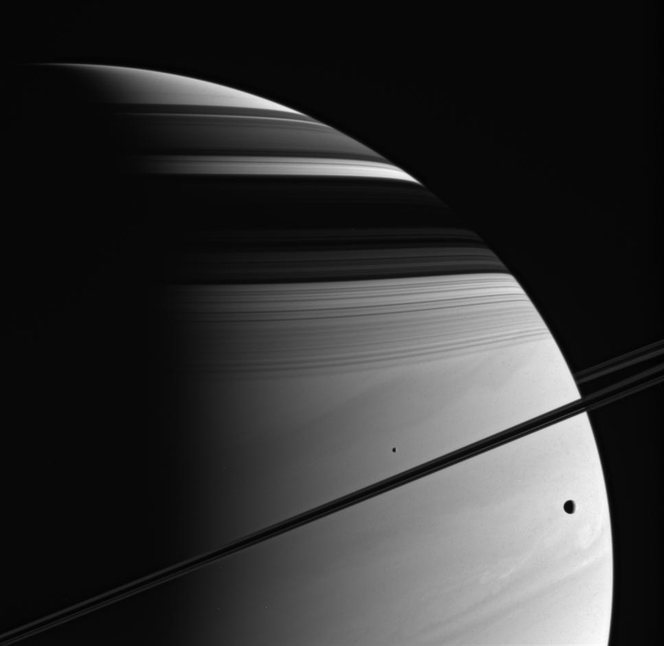 Tethys (at the right) and Mimas (near the center) are captured in this imag against Saturn's turbulent atmosphere.