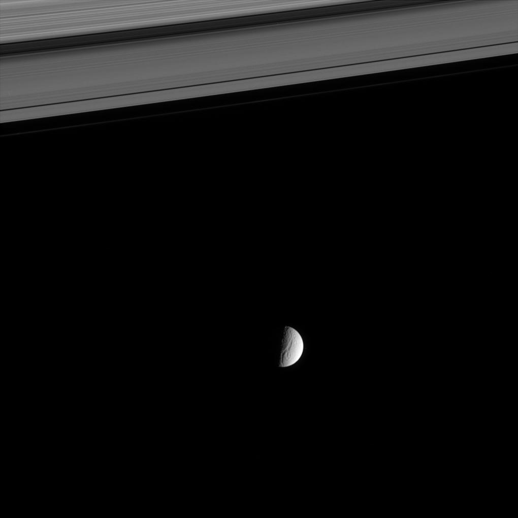 a distant view of Tethys beyond Saturn's rings