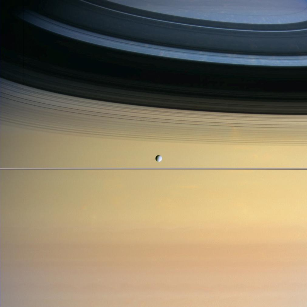 Saturn's small moon Dione with Saturn imposing in the background