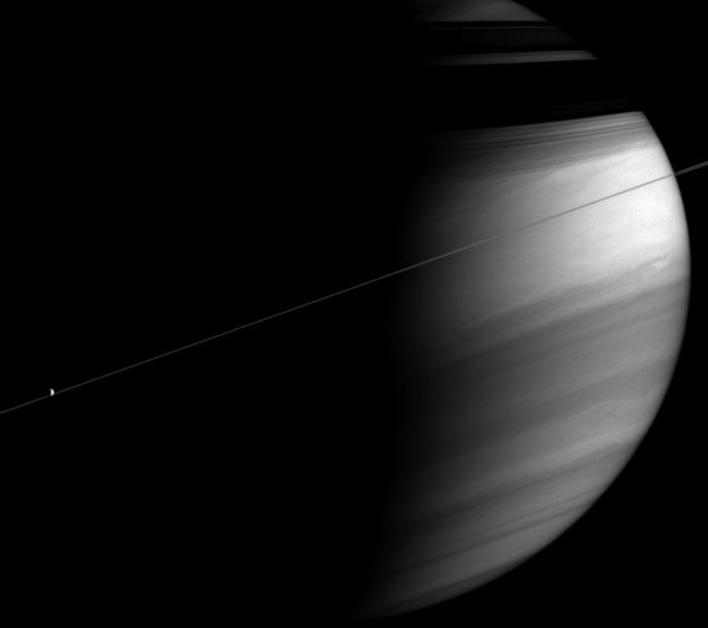Saturn with its rings casting shadows on the planet. Dione also appears here.