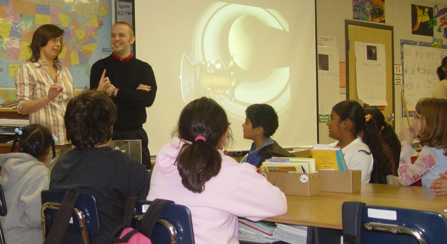 Two Cassini Science team members talking to students