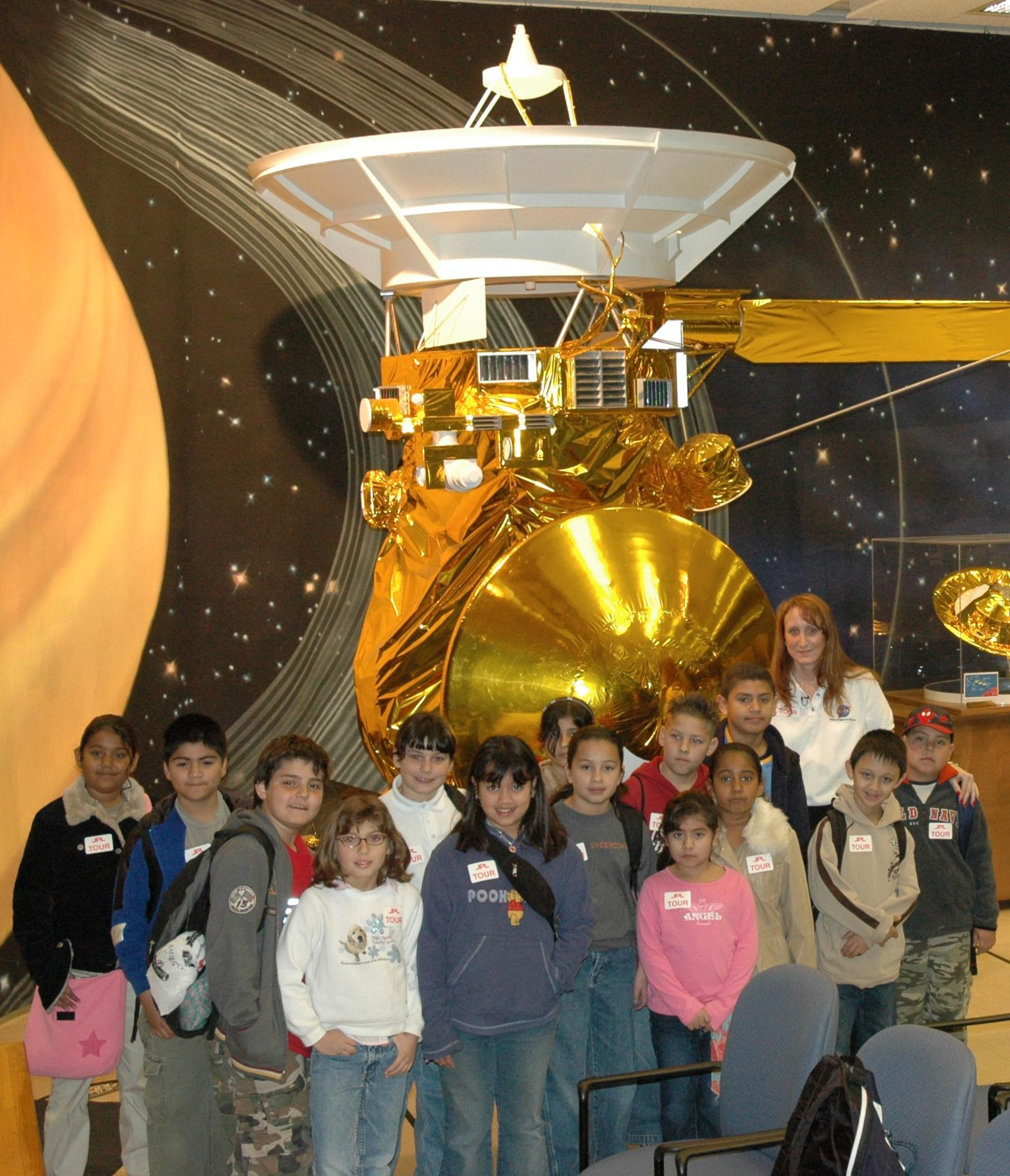 Students and their teacher pose in front of a half-scale model of Cassini