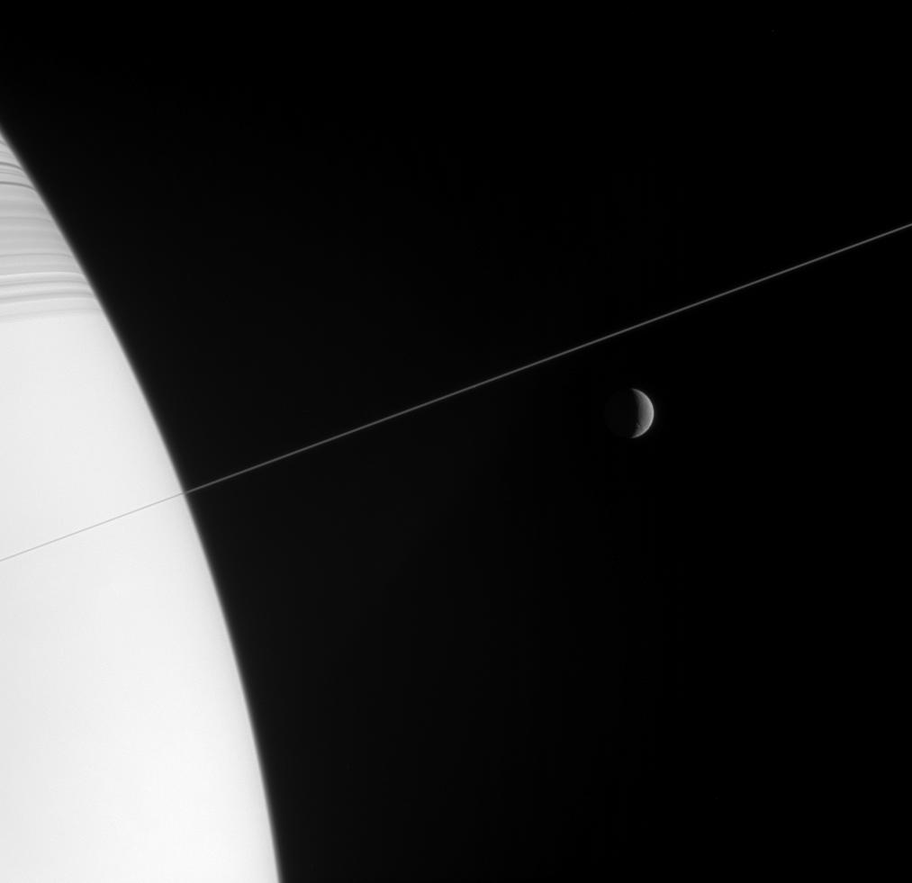 Saturn and a nearly edge-on view of the rings, along with Rhea