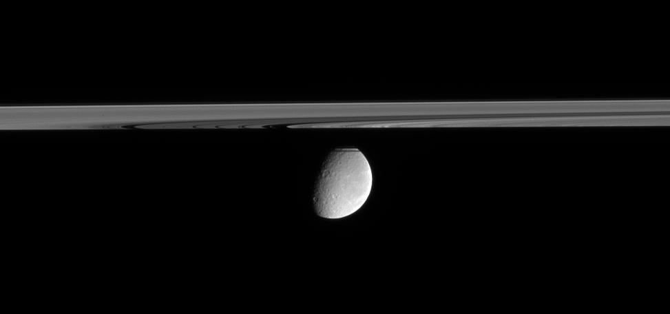 Rhea floats in the distance, peeking out from behind Saturn's partly shadowed rings