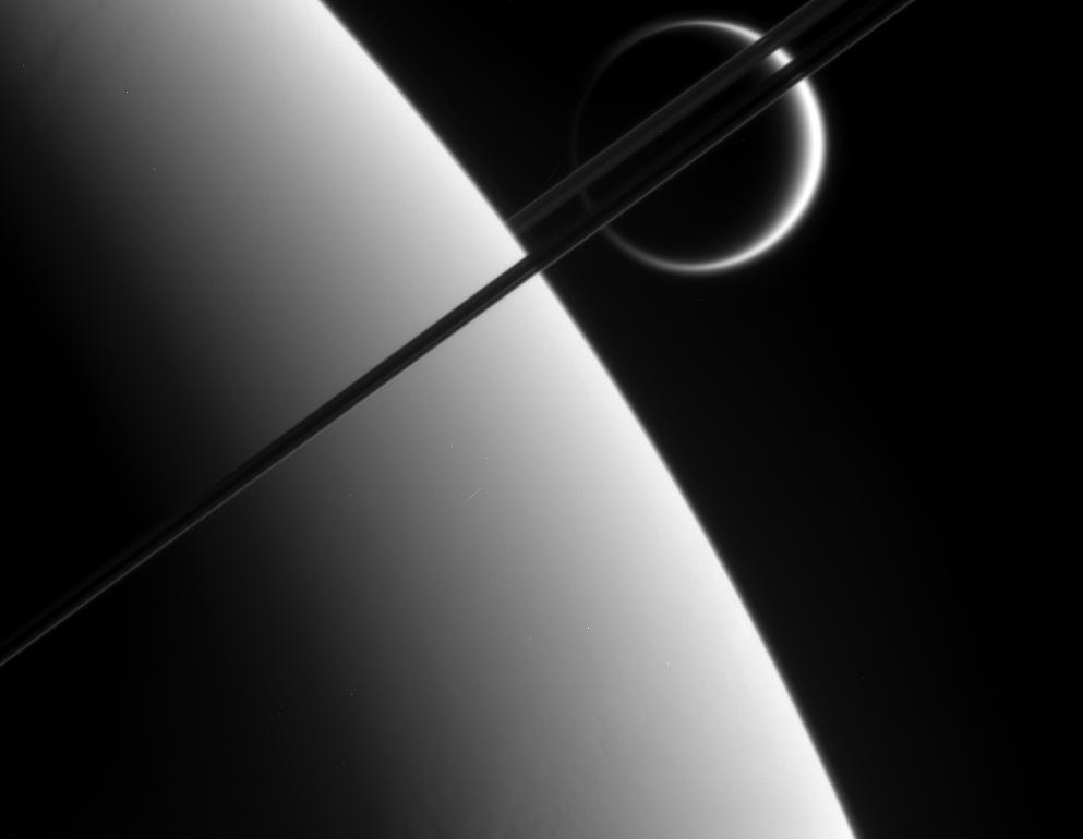 Titan in the distance beyond Saturn and its dark and graceful rings