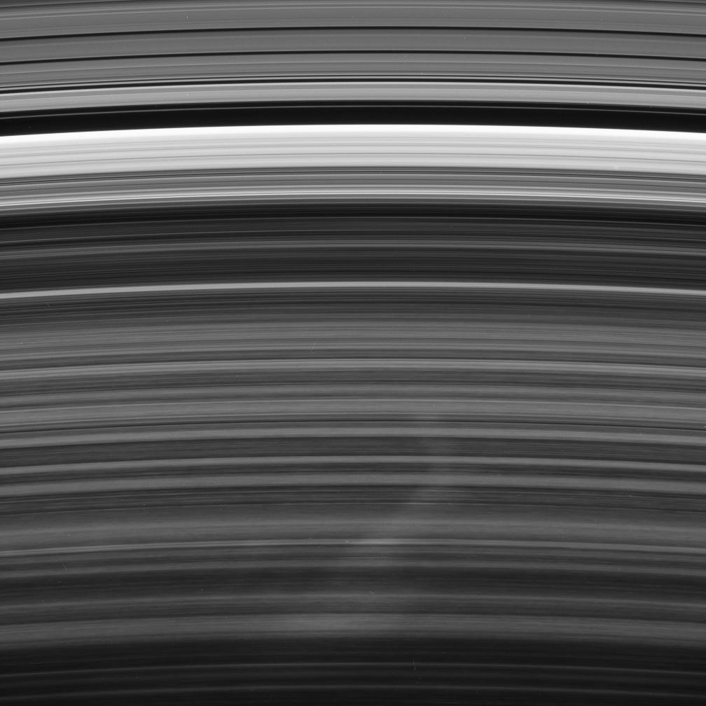 A bright spoke extends across the unilluminated side of Saturn's B ring