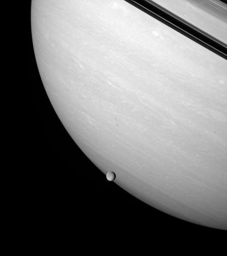 Rhea brushes the stormy face of Saturn