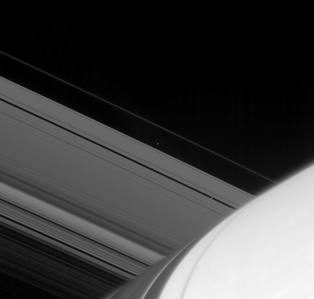 Atlas and Pan emerge from the far side of Saturn