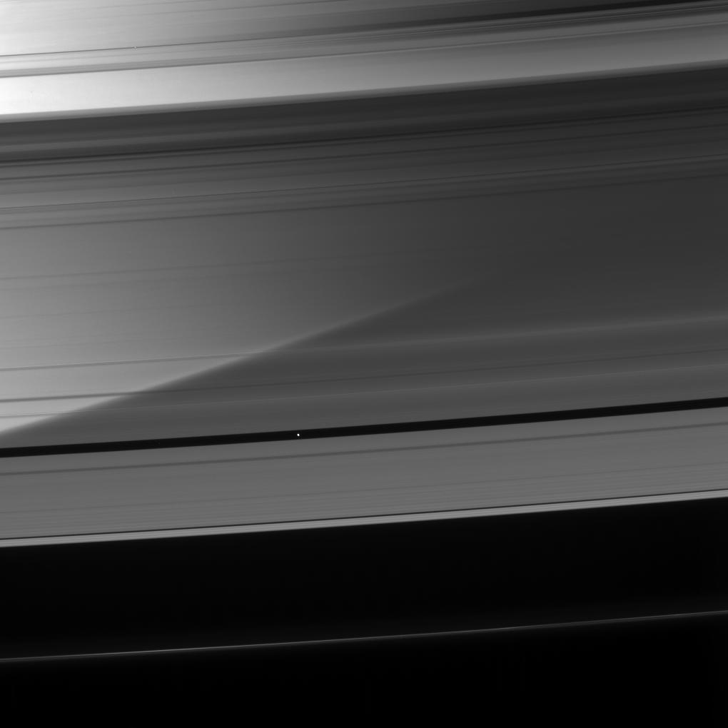 Saturn is visible through the A ring as Pan coasts along its private corridor