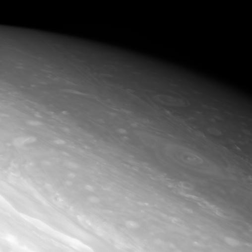 Giant vortices swirl in the dim northern latitudes of Saturn.