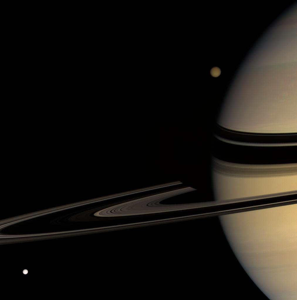 Titan emerges from behind Saturn, while Tethys streaks into view.