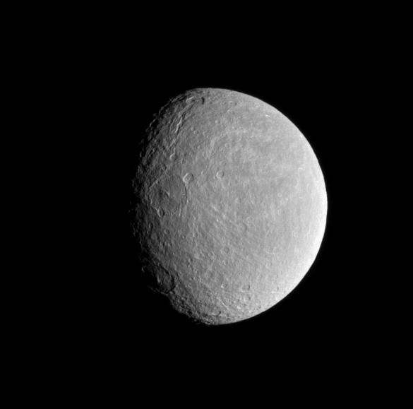 The sun's low angle near the terminator highlights the topography of craters within Rhea's wispy terrain.