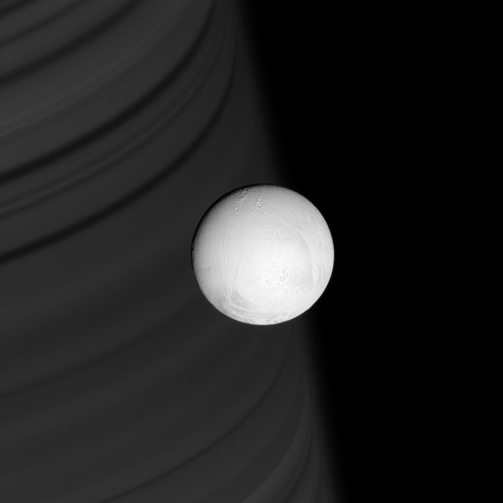 Enceladus in front of a backgdrop of Saturn's rings
