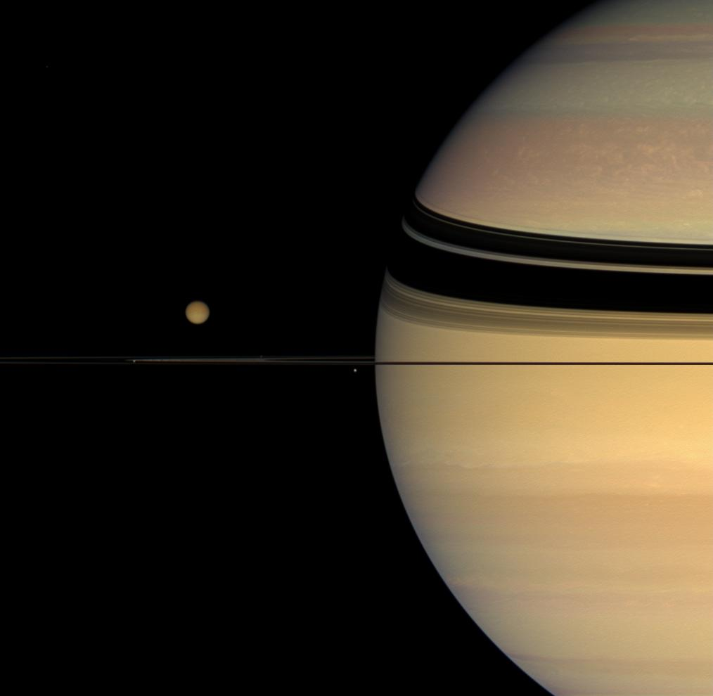 Four moons huddle near Saturn's multi-hued disk.