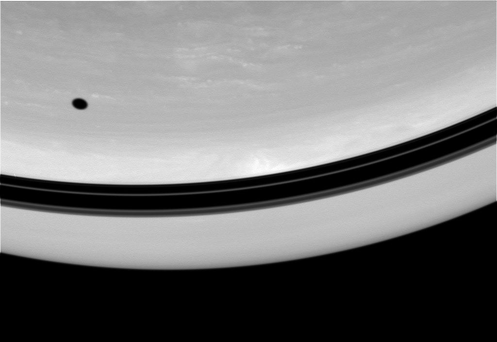 The shadow of Tethys drifts across the face of Saturn