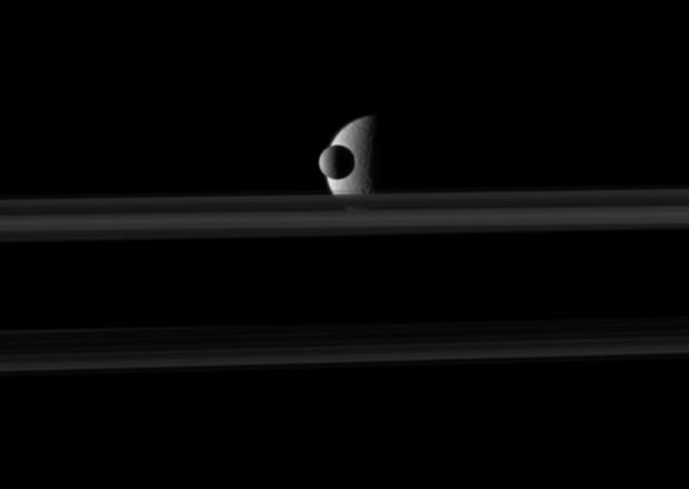 The small moon Mimas passes in front of the larger moon Rhea, which is partly obscured by Saturn's rings, in this movie from NASA's Cassini spacecraft.