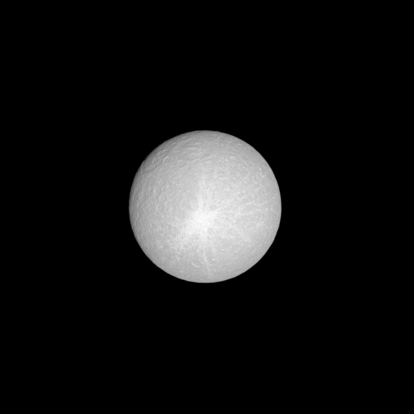 Lit brilliantly by the sun, the moon Rhea shows off its huge ray crater.