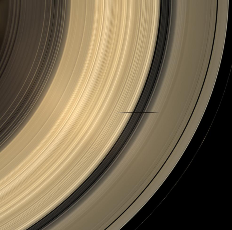 The shadow of Saturn's moon Mimas dips onto the planet's rings