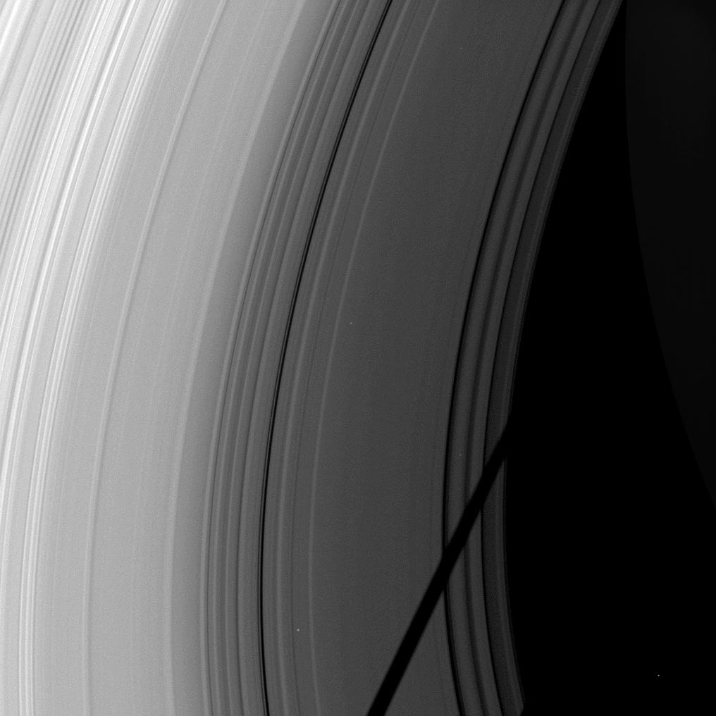 The shadow of the moon Tethys cuts across Saturn's rings