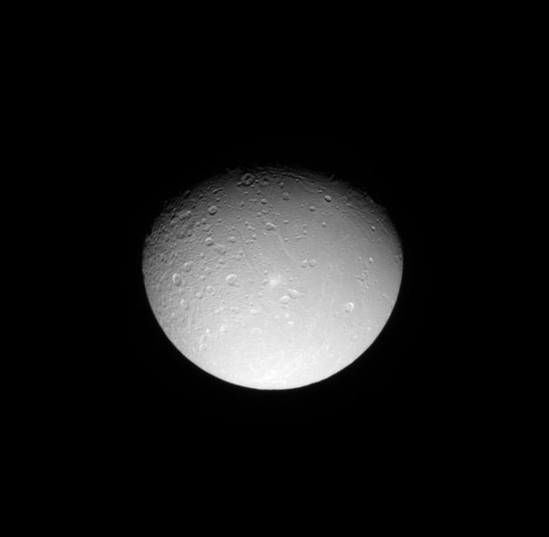 The Cassini spacecraft looks down on the cratered northern leading hemisphere of Dione, showing the moon's pockmarked surface.