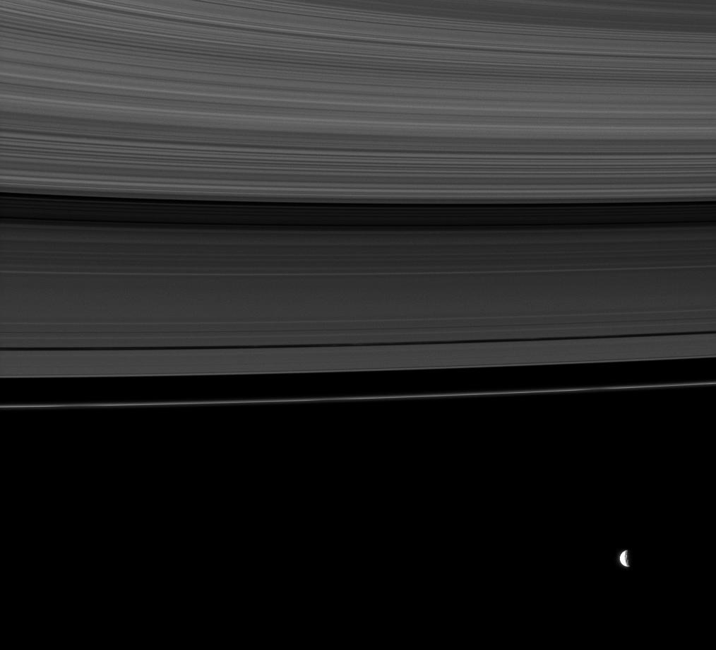 The rings share this view with Mimas, a moon whose gravity influences the rings.