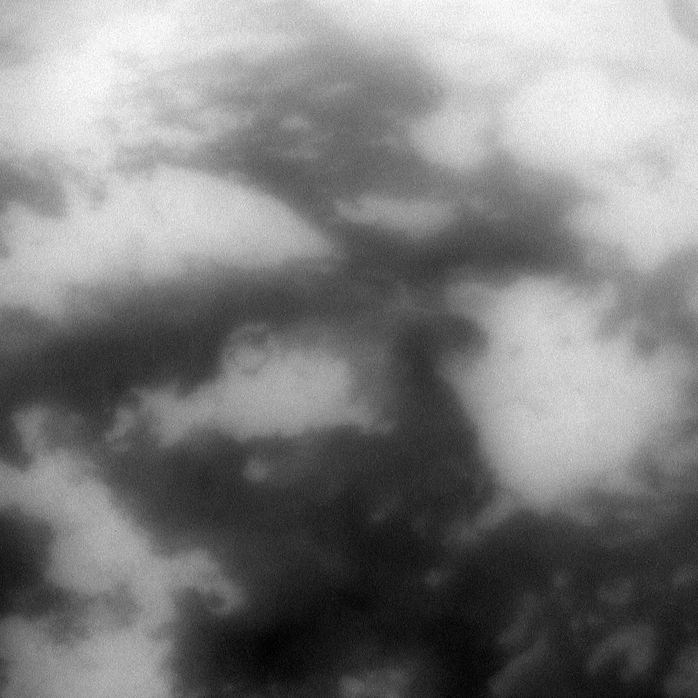 The low albedo feature known as Senkyo is visible through the haze of Titan's atmosphere