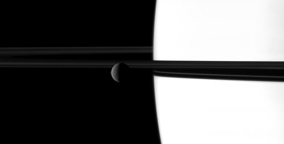 The small moon Janus overtakes the larger moon Rhea in a dance played out before Saturn and its rings.
