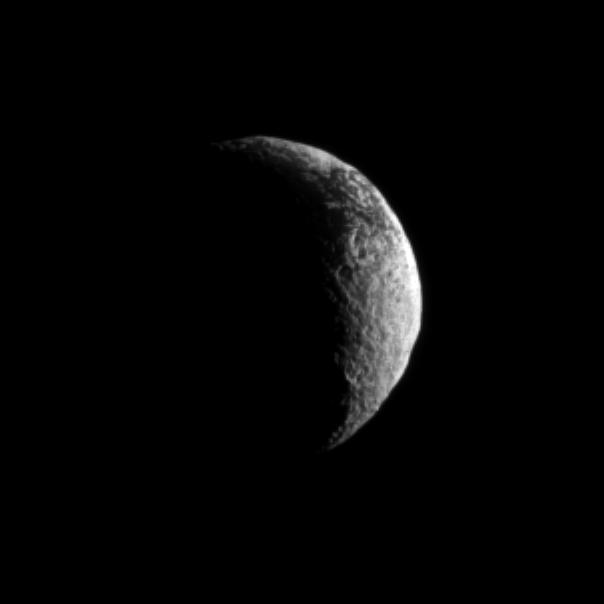 The Cassini spacecraft looks toward a crescent of Saturn's dark and light moon, Iapetus.