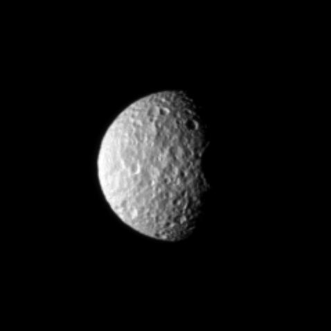 The oblate moon Mimas displays the cratered surface of its anti-Saturn side.