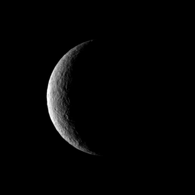 The Cassini spacecraft captures a crescent of crater-covered surface on the moon Rhea.