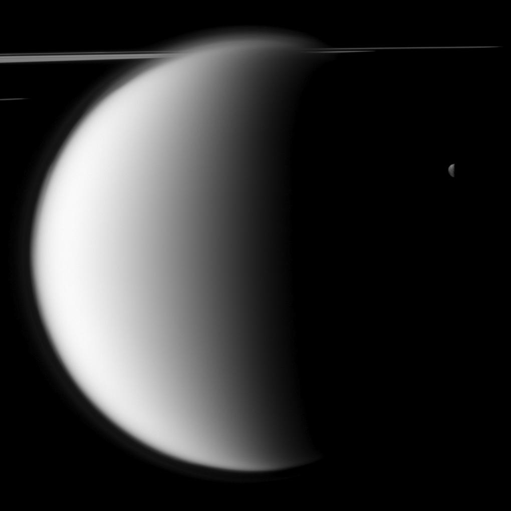 "The Cassini spacecraft captures a ""mutual event"" between Titan and Mimas in front of a backdrop of the planet's rings."