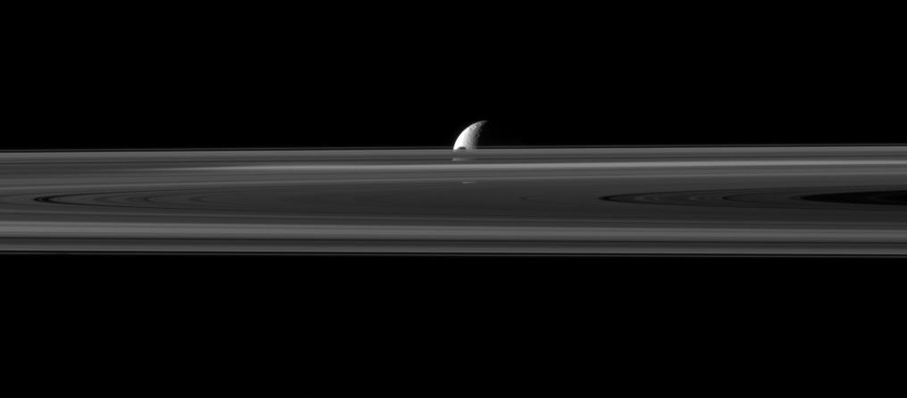 The small moon Janus is almost hidden between the planet's rings and the larger moon Rhea.