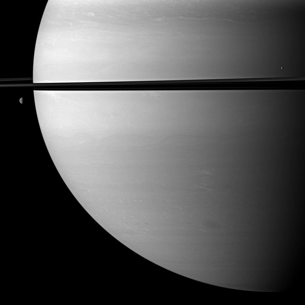 Two moons orbit serenely before Saturn while large storms churn through the planet's southern hemisphere.