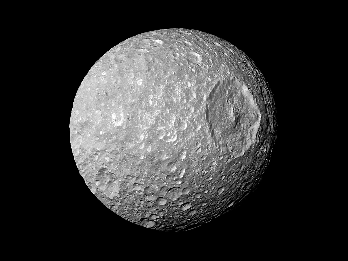 "In this view captured by NASA's Cassini spacecraft on its closest-ever flyby of Saturn's moon Mimas, large Herschel Crater dominates Mimas, making the moon look like the Death Star in the movie ""Star Wars."""