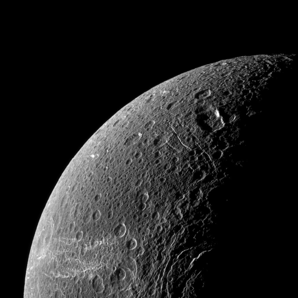 Wispy terrain reflects sunlight brightly in the lower left of this Cassini image of the northern latitudes of Saturn's moon Dione.