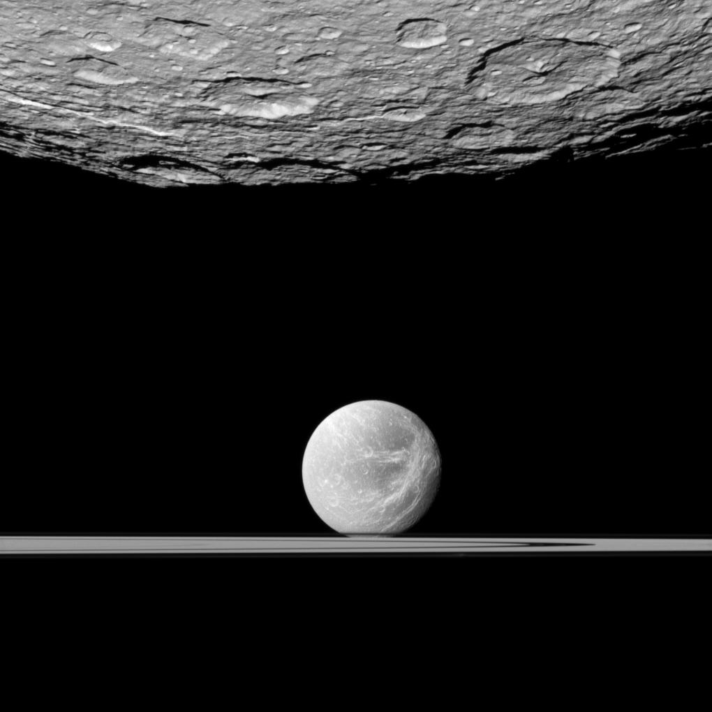 Rhea in foreground at top and Dione and the rings below