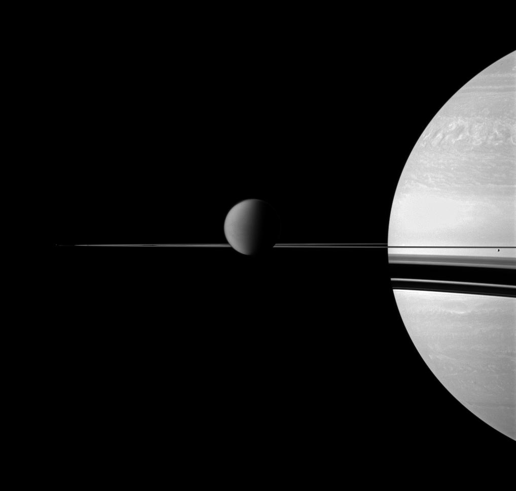 The Cassini spacecraft views Saturn with a selection of its moons in varying sizes.