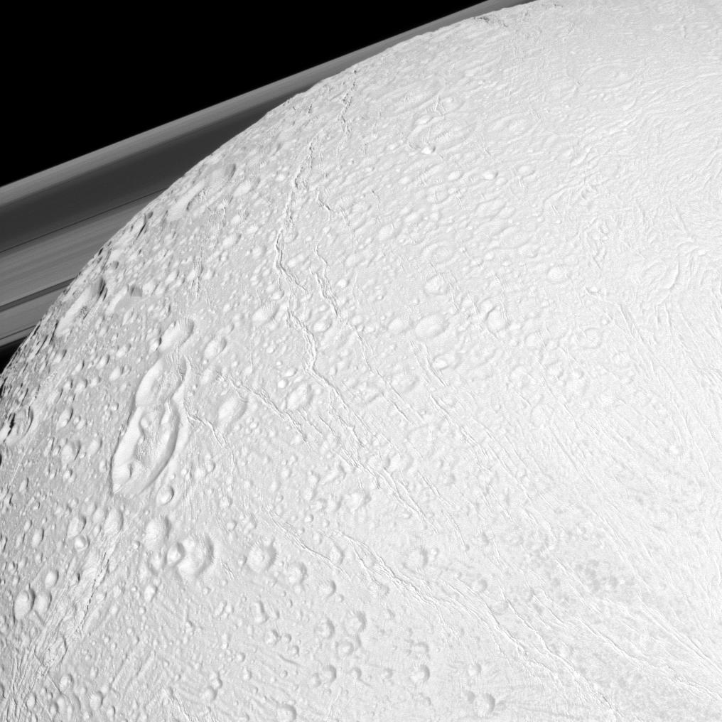 The Cassini spacecraft watches over the northern latitudes of Saturn's geologically active moon Enceladus while the planet's rings peek through in the distance in this snapshot.