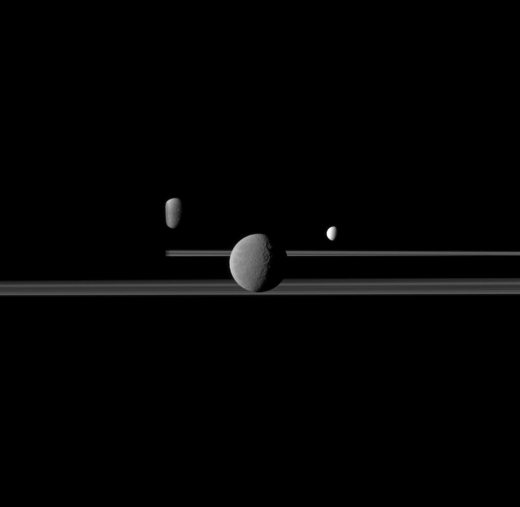 Rhea, Dione and Enceladus - set against the darkened night side of Saturn