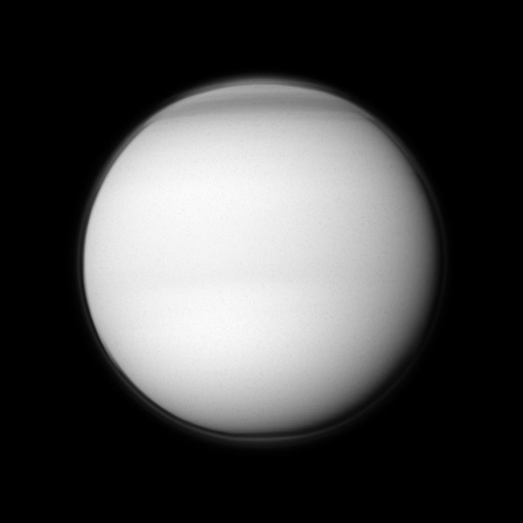 The Cassini spacecraft examines Titan's north polar hood, the part of the atmosphere of Saturn's largest moon appearing dark at the top of this image.