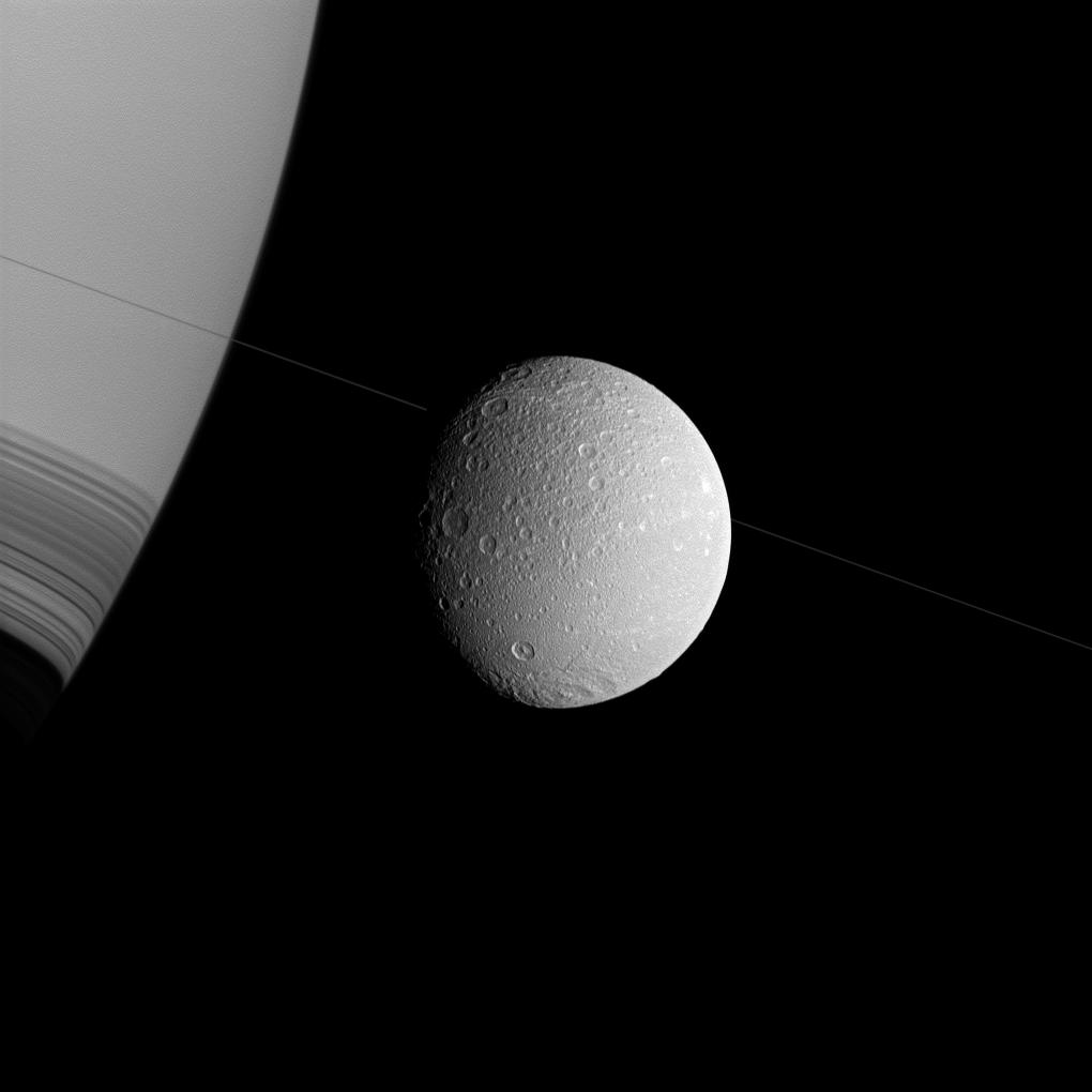 Saturn, Dione and the thin diagonal line of the planet's rings