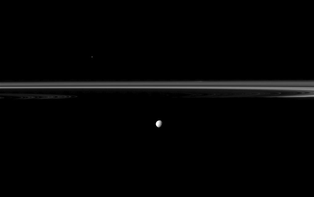 Saturn's moon Mimas joins the planet's rings which appear truncated by the planet's shadow in this Cassini spacecraft image.