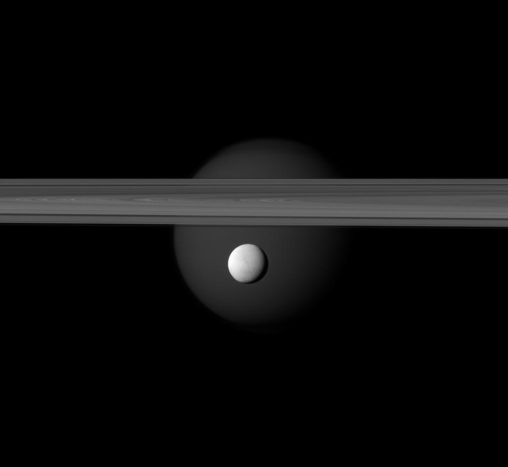 Enceladus appears before Saturn's rings while Titan looms in the distance