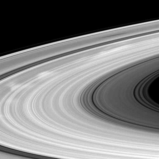 Bright spokes and the shadow of a moon grace Saturn's B ring in this Cassini spacecraft image.