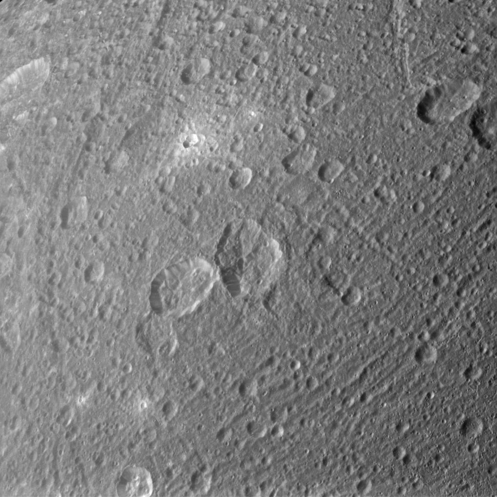 Ejected material appears bright around some of Dione's craters