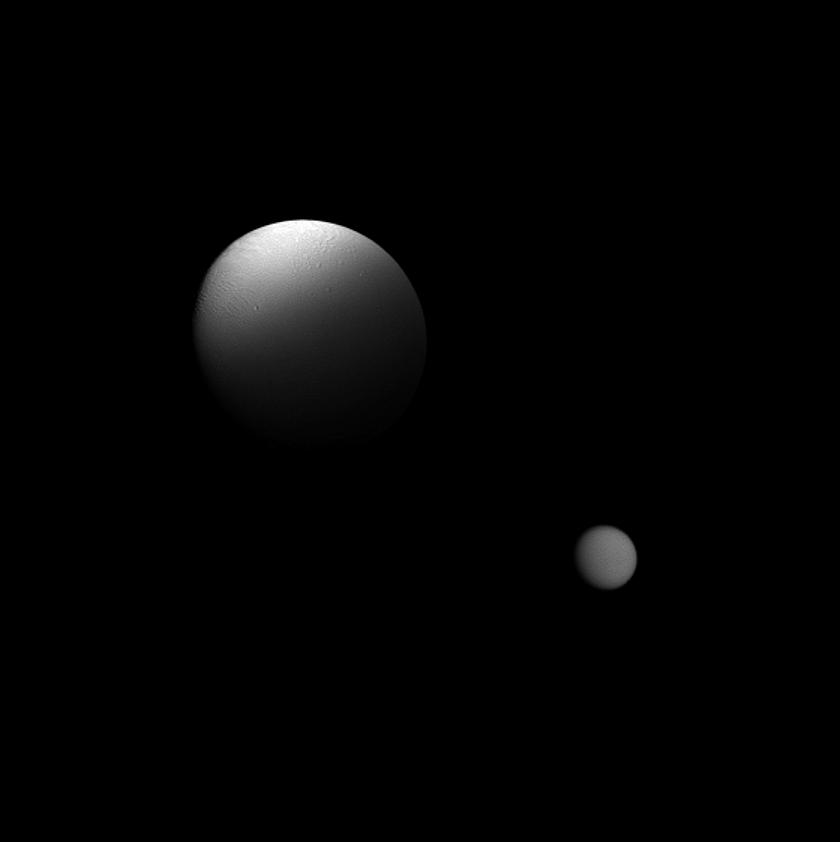 Saturn's moon Enceladus is partially eclipsed by the planet in this Cassini spacecraft view which also features the moon Titan in the distance.