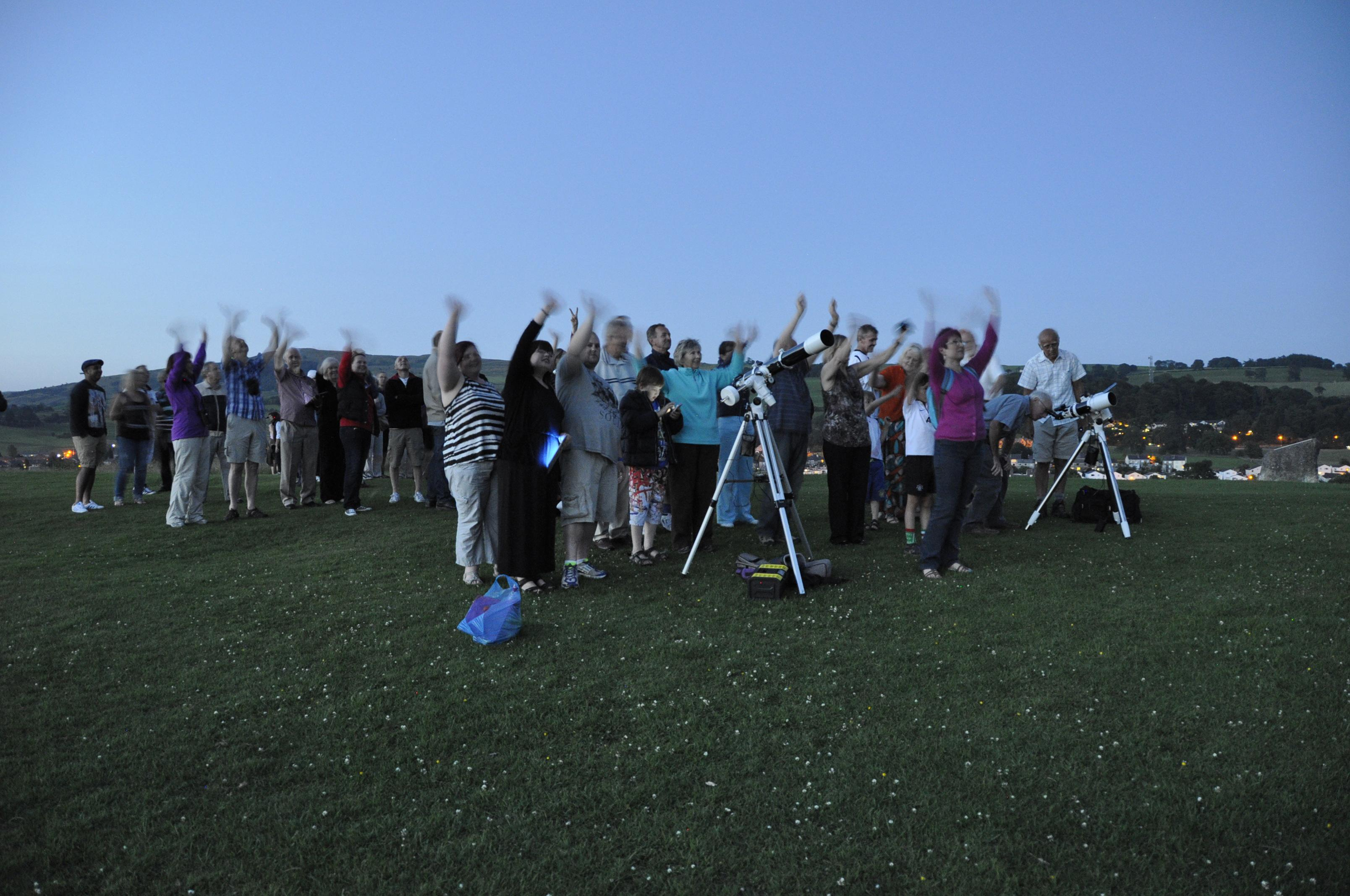 Telescopes, telephone and tablets at the ready, a group of amateur astronomers gathers under twilight skies to wave at Saturn on July 19, 2013. Their gathering in the town of Kendal in England's Cumbria district was one of many international celebrations as Earth was imaged from deep space by NASA's Cassini spacecraft.
