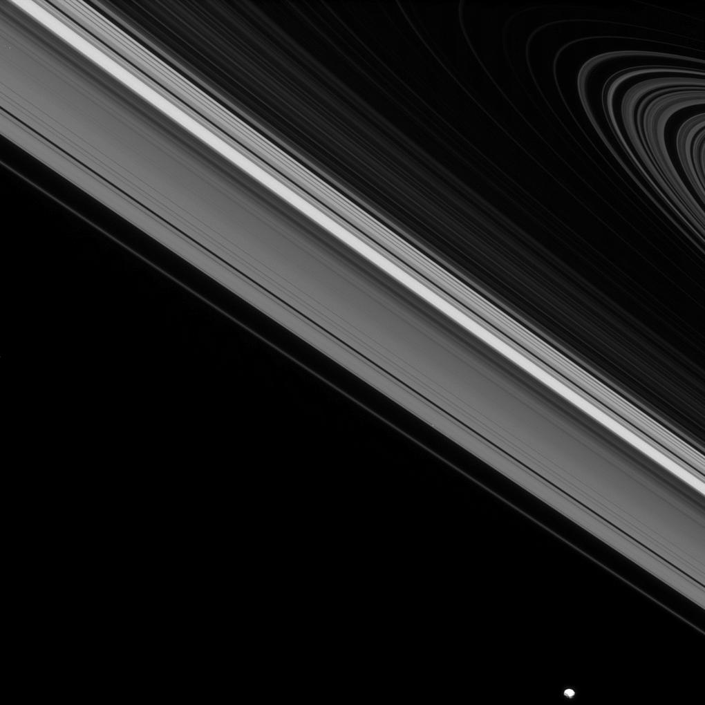 While the moon Epimetheus passes by, beyond the edge of Saturn's main rings, the tiny moon Daphnis carries on its orbit within the Keeler gap of the A ring.