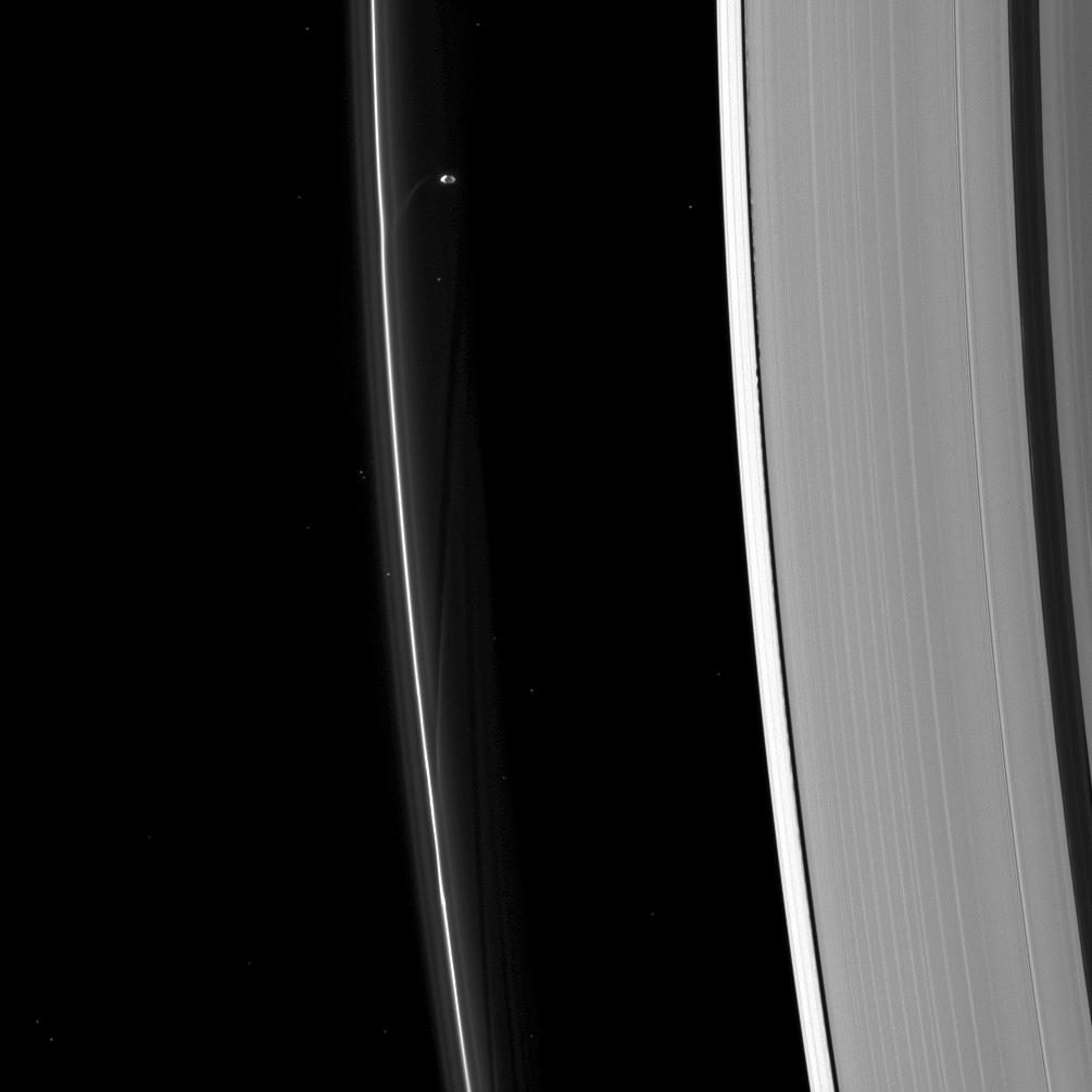 Here Prometheus is seen sculpting the F ring while Daphnis (too small to discern in this image) raises waves on the edges of the Keeler gap.