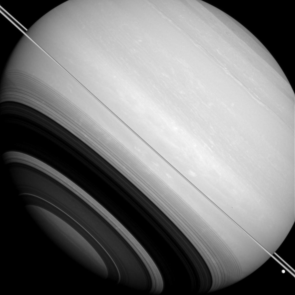Saturn is circled by its rings, as well as by the moons Tethys and Mimas.